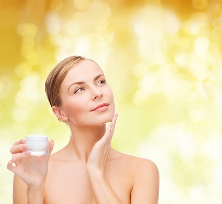 bodycare: cosmetics, health and beauty concept - beautiful woman applying cream on her skin