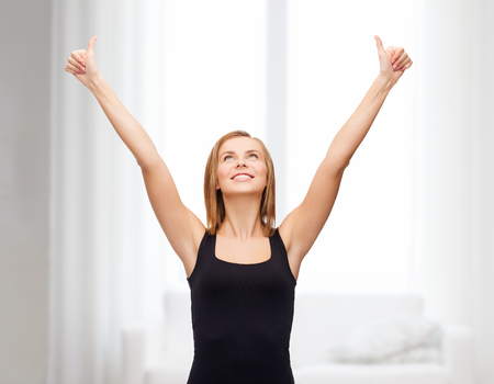 tank top: t-shirt design, happy people concept - smiling woman in blank black tank top showing thumbs up Stock Photo