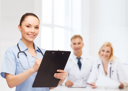 prescribing: healthcare and medicine concept - smiling female doctor or nurse with stethoscope and clipboard