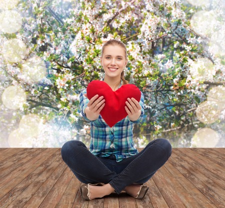 happiness and people concept - smiling young woman in casual clothes sitiing on floor and holding red heart photo