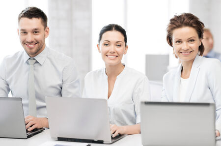 group picture: picture of group of people working with laptops in office Stock Photo
