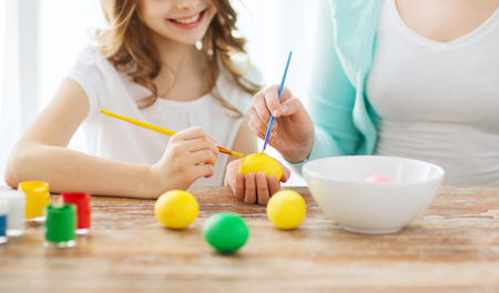 tinkering: easter, family, holiday and child concept - close up of little girl and mother coloring eggs for easter