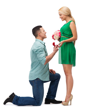 happiness, proposal, engagement and celebration concept - smiling couple with flower bouquet and ring in a box