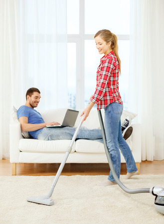 home, relations and cleaning concept - smiling woman with vacuum and young man with laptop at home photo