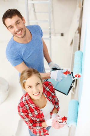painting house: repair, building and home concept - smiling couple painting wall at home
