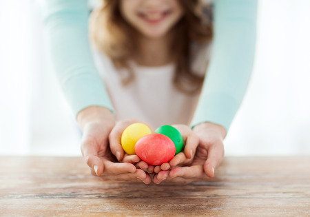 easter, family, holiday and child concept - close up of little girl and mother holding colored eggs photo