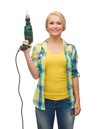 repair, construction and maintenance concept - smiling woman with drill machine photo