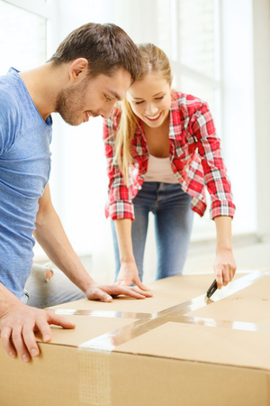 repair, building and home concept - smiling couple opening big cardboard box photo