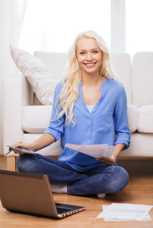 tax, finances, technology, home and happiness concept - smiling young woman with papers, laptop computer and calculator at home photo