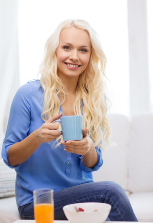 healthcare, food, home and happiness concept - smiling woman with cup of tea, glass of juice and bowl of muesli having breakfast photo