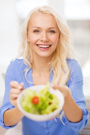 healt: healt, dieting, home and happiness concept - smiling young woman with green salad at home