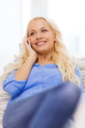 home, technology and communication concept - smiling woman with smartphone lying on couch at home photo