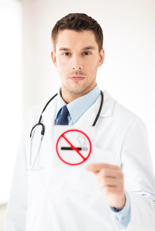 restrictions: male doctor holding no smoking sign in hands