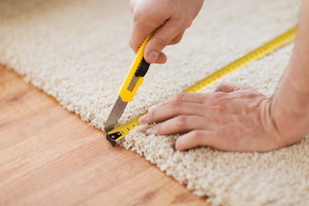 carpet and flooring: repair, building and home concept - close up of male hands cutting carpet with blade