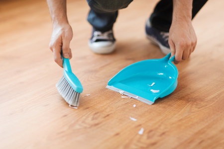 brooming: cleaning and home concept - close up of male brooming wooden floor with small whisk broom and dustpan