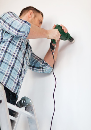 renovating: repair, building and home concept - close up of male with electric drill making hole in wall