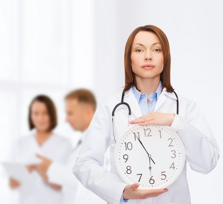 schedule appointment: healthcare and medicine concept - calm female doctor with wall clock and stethoscope Stock Photo