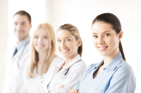 attractive female doctor or nurse in front of medical group Stock Photo