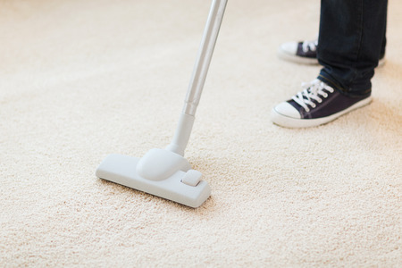 carpet and flooring: cleaning and home concept - close up of male hoovering carpet Stock Photo