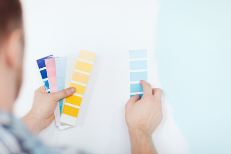 repair, building, technology and home concept - close up of male with color pallets choosing color Stok Fotoğraf