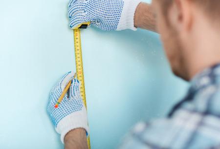 metro de medir: reparación, construcción y concepto de hogar - cerca del varón en los guantes de medición de la pared con cinta adhesiva Foto de archivo