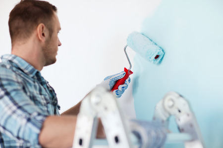 construction work: repair, building and home concept - close up of male in gloves holding painting roller