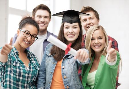 diploma: concepto de educaci�n - ni�a feliz en la tapa de graduaci�n con el diploma y los estudiantes Foto de archivo