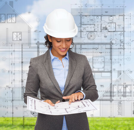 building plans: building, developing, consrtuction and architecture concept - smiling businesswoman in white helmet pointing finger to blueprint