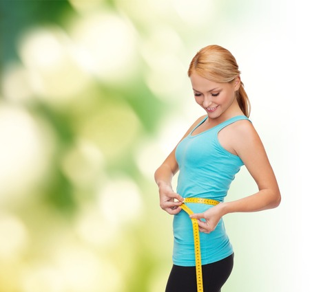 measure waist: diet, sport and heath concept - beautiful sporty woman with measuring tape