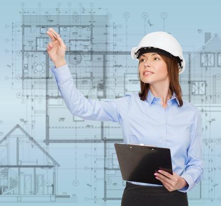 gente exitosa: construir, desarrollar, consrtuction y arquitectura concepto - la sonrisa de negocios en el casco blanco con el sujetapapeles que señala el dedo