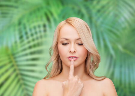 eco sensitive: health and beauty concept - beautiful woman touching her lips
