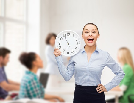 high school teacher: business, education and time concept - attractive teacher with wall clock