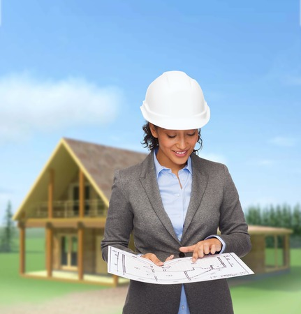 american dream: building, developing, consrtuction and architecture concept - smiling businesswoman in white helmet pointing finger to blueprint