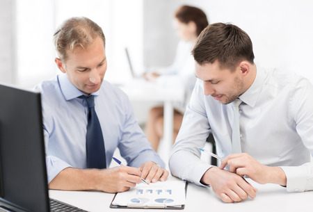 accountancy: business and office concept - businessmen with notebook discussing graphs on meeting Stock Photo