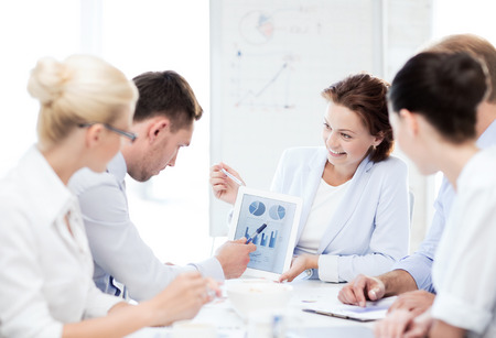 accountancy: friendly business team discussing graphs in office