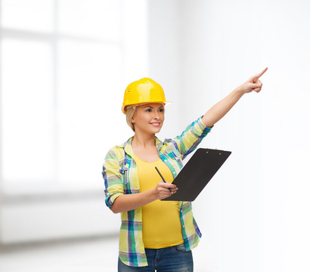safety gear: repair, construction and maintenance concept - smiling woman in helmet with clipboard pointing finger Stock Photo