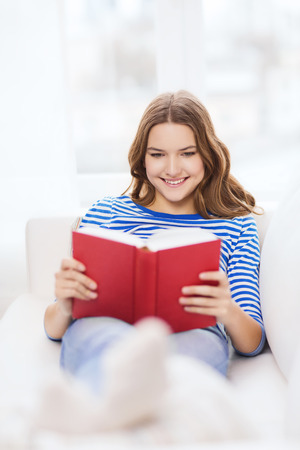 leasure: leasure and home concept - smiling teenage girl woman reading book and sitting on couch at home