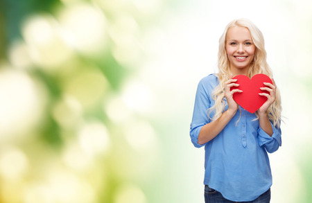 family health: happiness, health and love concept - smiling woman with red heart