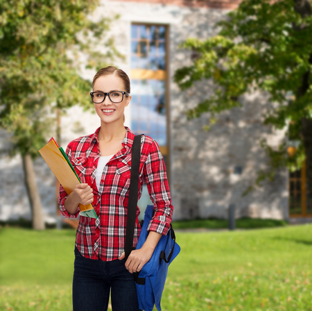 education and people concept - female student in eyeglasses with bag and folders