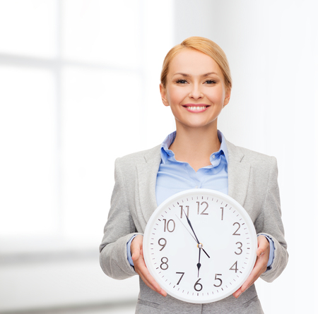 running out of time: business and time concept - attractive businesswoman with wall clock