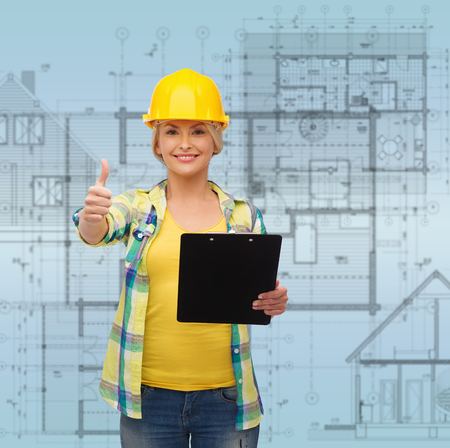 safety gear: repair, construction and maintenance concept - smiling woman in helmet with clipboard showing thumbs up
