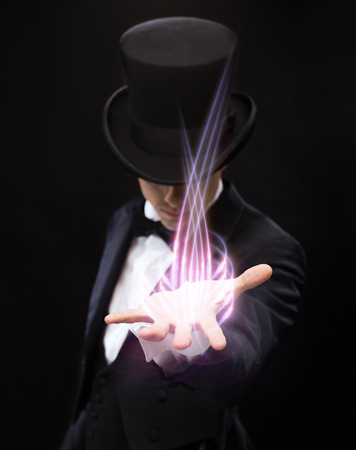 illusionist: magic, performance, circus, show and advertisement concept - magician holding something on palm of his hand