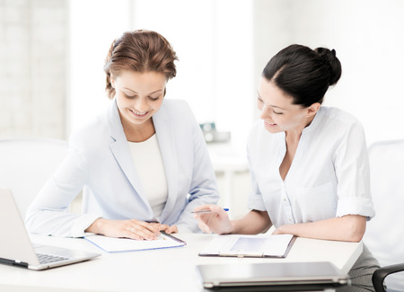 accountancy: business and office concept - picture of two smiling businesswomen working in office