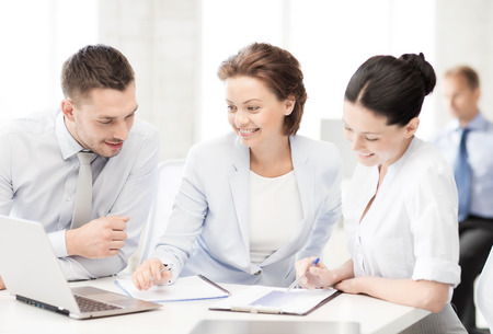accountancy: business and office concept - smiling business team discussing something in office Stock Photo