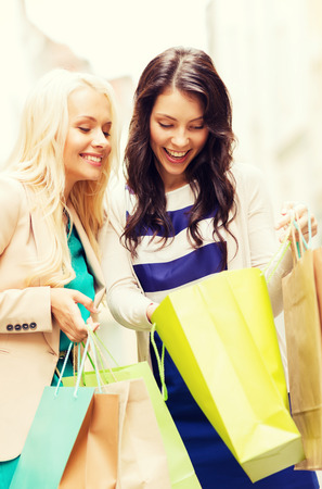 overspending: shopping and tourism concept - beautiful girls with shopping bags in city