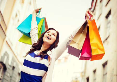 overspending: shopping and tourism concept - beautiful woman with shopping bags in city