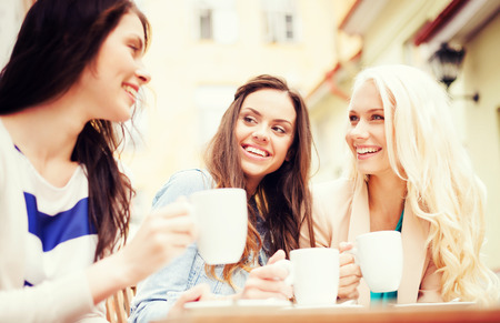 having a break: holidays and tourism concept - beautiful girls drinking coffee in cafe Stock Photo