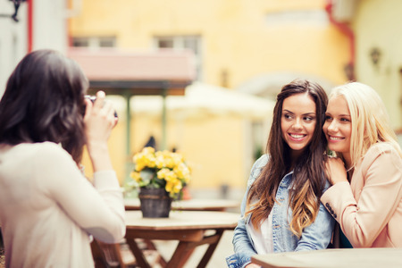 digi: holidays and tourism concept - beautiful girls taking picture in cafe in city Stock Photo