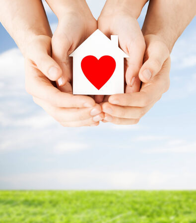 charity, real estate and family home concept - closeup picture of male and female hands holding white paper house with red heart photo