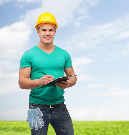 repair, construction and maintenance concept - smiling man in helmet with clipboard photo